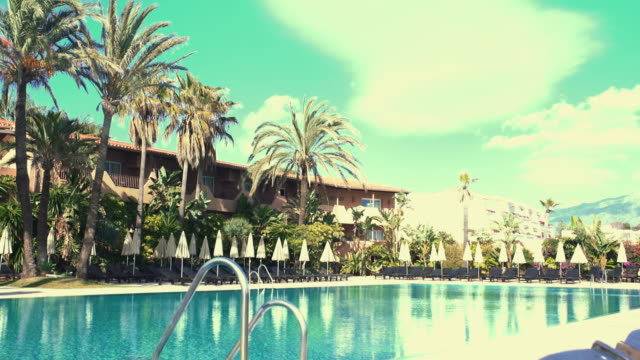 Idilic terrace of hotel with swimming pool and deck chairs