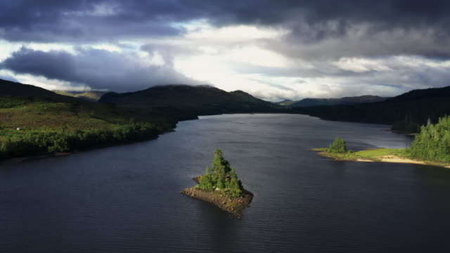 idyllic aerial view flying backwards from an island in a loch, scottish highlands, united kingdom - named wilderness area stock videos & royalty-free footage