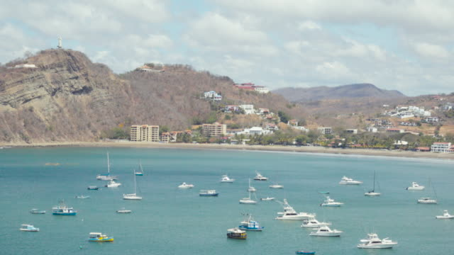 idyllic beach bay coastline with yachts at san juan del sur. coast line from an aerial point of view. we can see the fisher boats on the blue pacific sea and the jesus statue on the left top. sunny day with some clouds that shade the landscape. - nicaragua stock videos and b-roll footage