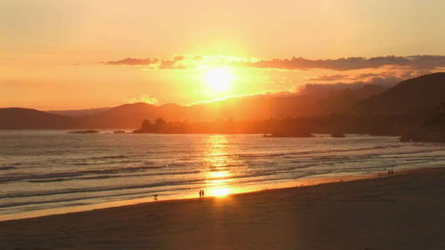 Idyllic California sunset of the coast of Pison Beach with people walking along the shore enjoying the beauty