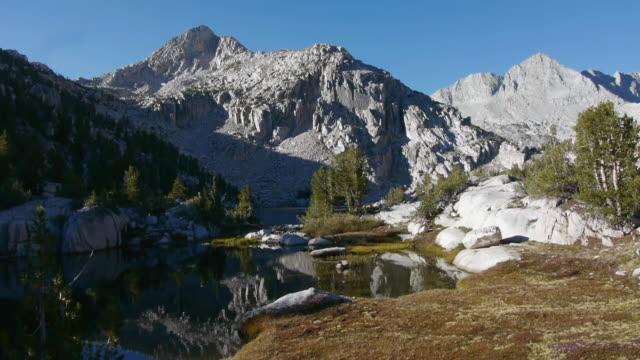 pan idyllic high sierra wilderness scene with lake & mountain peaks, kings canyon national park, sierra nevada mountains, california - area selvatica video stock e b–roll