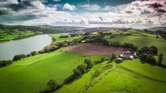 vidéos et rushes de aerial: paysage idyllique avec des champs verts et des fermes au pays de galles - végétation verdoyante