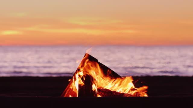 vidéos et rushes de idyllique bonfire coucher de soleil sur la plage - feu de camp