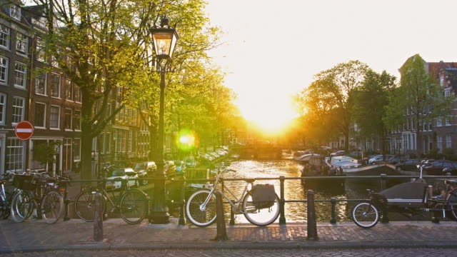 idyllic sunset over amsterdam river canal seen from picturesque bridge with street lamp and parked bikes - amsterdam stock videos & royalty-free footage