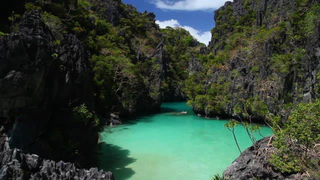 "vídeos de stock, filmes e b-roll de ""ws pan of idyllic tropical lagoon surrounded by plants and sharp limestone cliffs / small lagoon, miniloc island, bacuit archipelago, el nido, palawan, philippines "" - laguna"