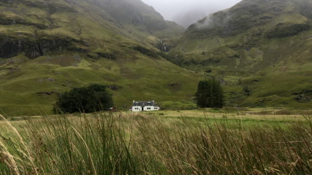 idyllic view of the scottish highlands with lonely house and waterfall. - コテージ点の映像素材/bロール