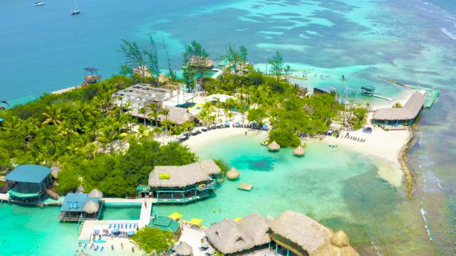 idyllic white sand beach little island in the caribbean sea in a sunny day, roatan, honduras. - tropical tree stock videos & royalty-free footage