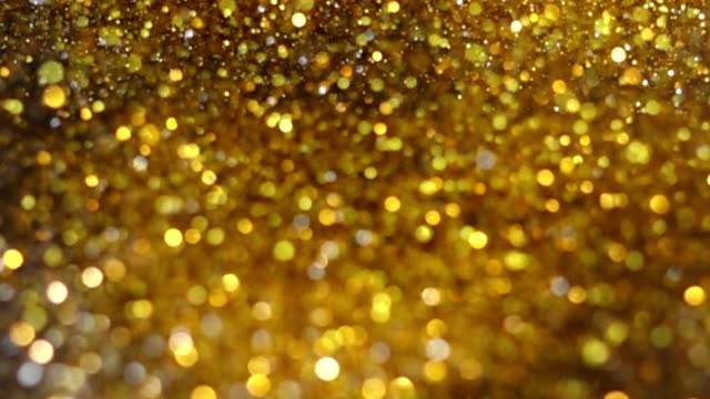 vídeos de stock e filmes b-roll de ig explosion golden glitter dust tiny reflect light in the air, dark black background - dourado cores