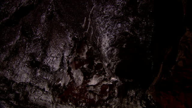 igneous rock lines the inside of a lava tube. - igneous stock videos & royalty-free footage