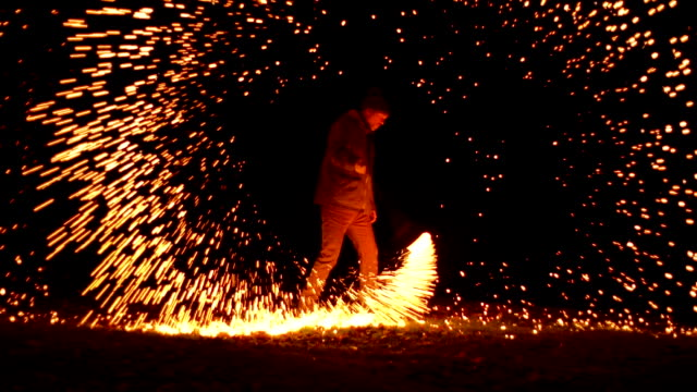 vídeos de stock e filmes b-roll de igniting wire wool and spinning it - turning