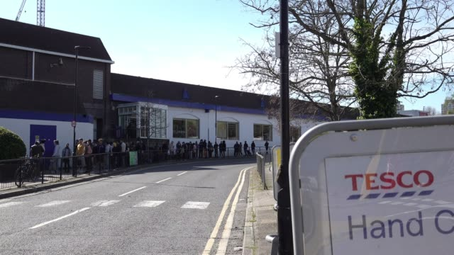 ignoring social distancing people queue closely together outside a tesco supermarket after being told to enact strict contact measures to prevent the... - enacting stock videos & royalty-free footage