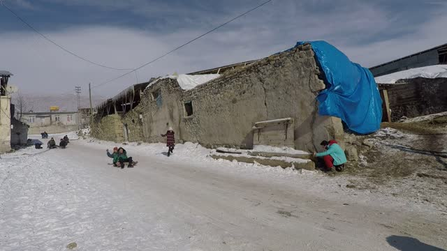 ignoring the freezing cold outside, children in rural neighborhoods of eastern turkey came together to sledge on snow covered roads. in erzurum... - cold temperature stock videos & royalty-free footage