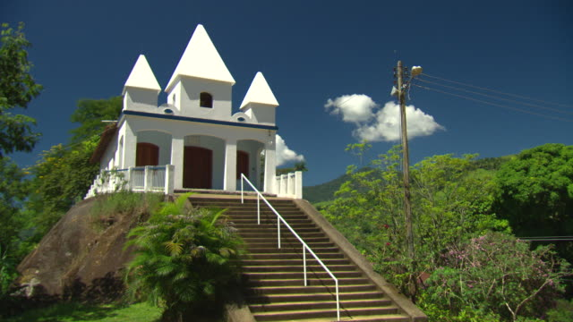 igreja de nossa senhora da penha paraty on costa verde coast white church sits on a small hill against a blue sky stairs leading up to the church - verde color stock videos & royalty-free footage