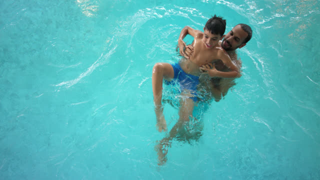 iindoor swimming pool area – tanned man in his 30s with short dark hair spends a great time together with his son and has lots of fun with his 8 years old pre-adolescent little boy in the turquoise blue thermal water - father is proud of his paternity - 30 39 years点の映像素材/bロール