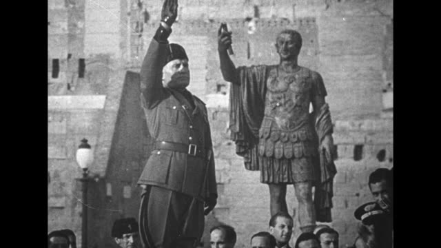 il duce benito mussolini issues fascist salute as he stands in front of statue of roman emperor nerva in the roman forum / italian troops march... - benito mussolini bildbanksvideor och videomaterial från bakom kulisserna