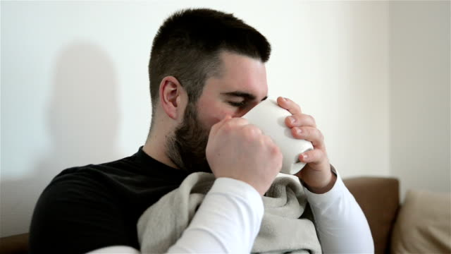 Ill man with flu drinking tea