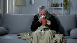Ill pensioner sneezing and drinking hot beverage, treating influenza, flu season