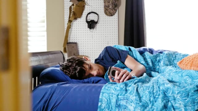 vídeos de stock e filmes b-roll de ill teenage boy uses smartphone while in bed - mensagem sms