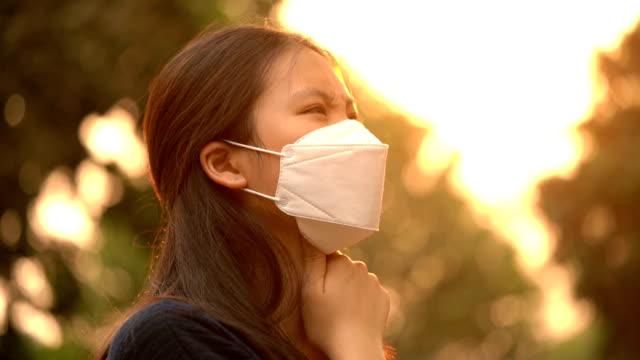 オレンジ色の太陽光で大気汚染マスクで咳をする mo の病気の女性 - film moving image点の映像素材/bロール