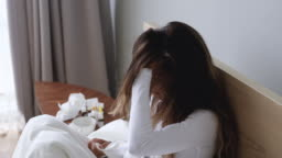 Ill woman got flu sneezing in tissue sit on bed