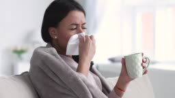 Ill young african woman covered with blanket sneezing blowing nose