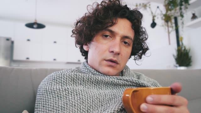 krank, junger mann mit grippe blick in die kamera. - cold temperature stock-videos und b-roll-filmmaterial