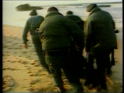 illegal immigrants illegal immigrants bv soldiers carrying body bag containing drowned immigrant along beach tms motor boat full of immigrants... - beach bag stock videos and b-roll footage