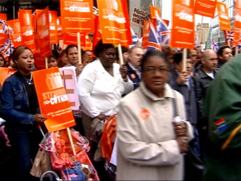 vídeos de stock, filmes e b-roll de illegal migrant worker protest march england london general views of protesters along carrying placards and blowing whistles sot - migrant worker