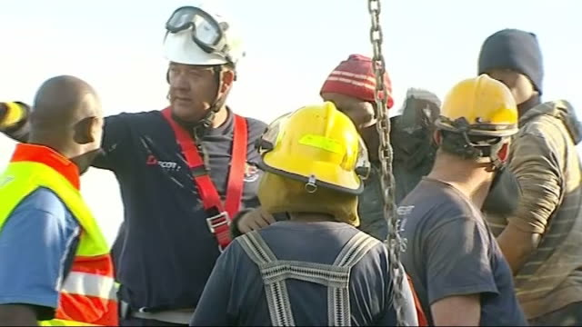 illegal miners rescued from disused gold mine; south africa: benoni: ext wide shot rescue workers at scene miner being rescued from disused gold mine... - 犯罪点の映像素材/bロール