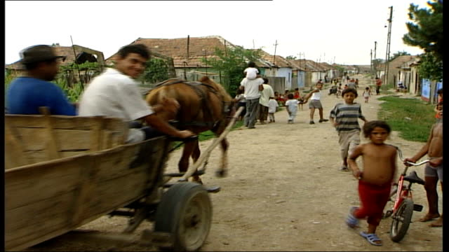 illegal traffic in babies exposed; children toward as men in horse-drawn cart away in village two girls playing girl and boy carrying bundle between... - horsedrawn stock videos & royalty-free footage
