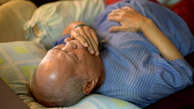 illness senior asian man coughing on bed - uncomfortable stock videos & royalty-free footage