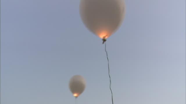 vídeos de stock e filmes b-roll de illuminated balloons float in a pastel sky. - pastel