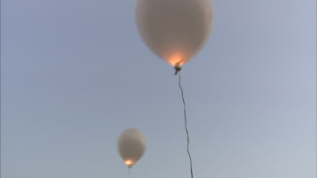 Illuminated balloons float in a pastel sky.