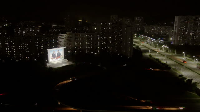 vidéos et rushes de illuminated billboard of the political leaders kim il sung and kim jong- residential buildings, traffic on kwangbok st. - wide shot at night. pyongyang, north korea, dprk - surveillance