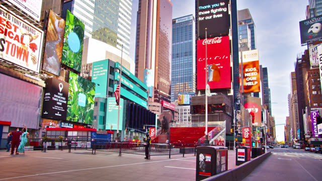 illuminated billboards in manhattan. statue of liberty posing with tourists. american flag. empty streets. new york. - broadway manhattan stock-videos und b-roll-filmmaterial