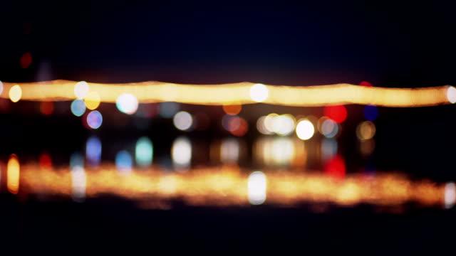 Beleuchtete Bokeh und Wasser Reflexion über den Fluss in der Nacht.