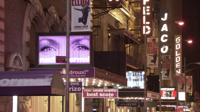 ms illuminated broadway marquees at buildings on 45th street, theatre district at night / manhattan, new york city, new york, usa - broadway manhattan stock-videos und b-roll-filmmaterial