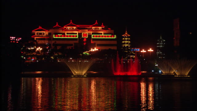 Illuminated buildings and fountains reflect on Li River at night