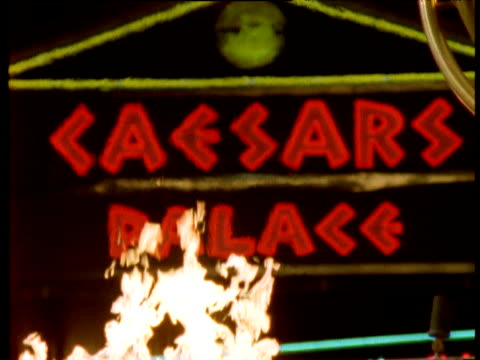 illuminated 'caesars palace' sign with flame rising from fire in foreground - gambling stock videos and b-roll footage