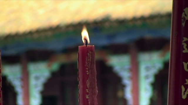 cu r/f illuminated candle and temple exterior, kunming, china - votive candle stock videos and b-roll footage