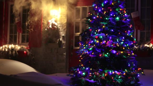 4k illuminated christmas tree at night during snowstorm - non urban scene stock videos & royalty-free footage