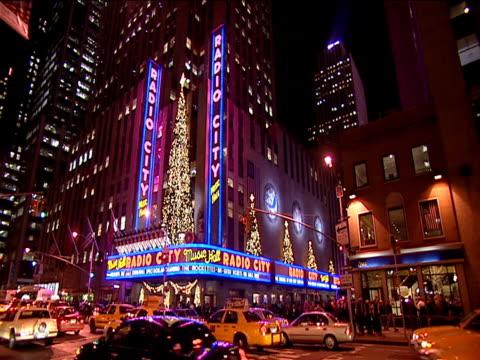 illuminated christmas trees decorating facade of radio city music hall - rockefeller center christmas tree stock videos & royalty-free footage