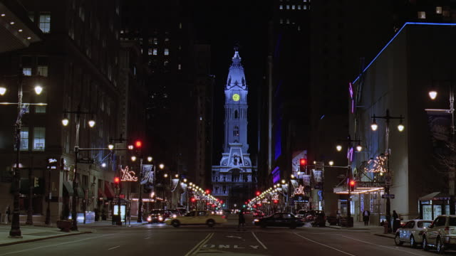 ws illuminated city hall in the distance at night while cars and pedestrians are seen passing / philadelphia, pennsylvania, united states - local government building stock videos & royalty-free footage