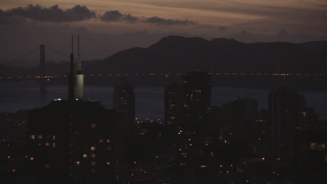 aerial illuminated cityscape, passing the transamerica pyramid and coit tower with a suspended bridge in the distance / san francisco, california, united states - coit tower stock videos & royalty-free footage
