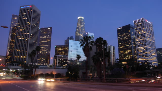 T/L WS Illuminated downtown skyscrapers with traffic in foreground, dusk to night / Los Angeles, California, USA
