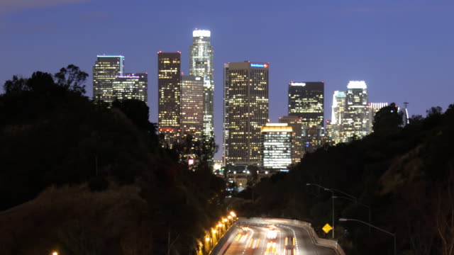 T/L WS Illuminated downtown skyscrapers with traffic on highway in foreground, dusk to night / Los Angeles, California, USA