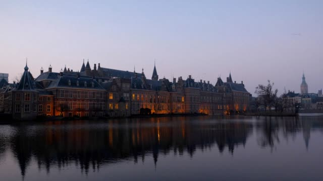 illuminated dutch parliament buildings in the hague, early morning. the netherlands - parliament building stock videos & royalty-free footage