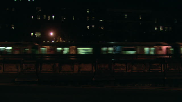 la illuminated elevated train passing at night, with lights of buildings beyond / new york city, new york, united states - moving past stock videos & royalty-free footage
