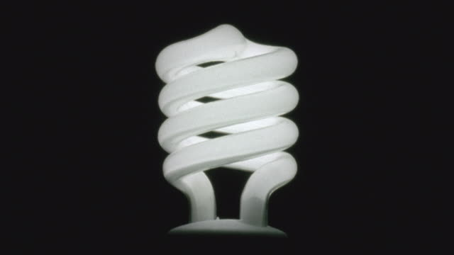 cu, illuminated energy saving light bulb on black background - energy efficient lightbulb stock videos and b-roll footage