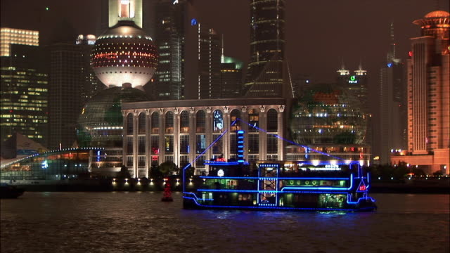 MS, illuminated ferry floating along buildings on river bank at night, Shanghai, China